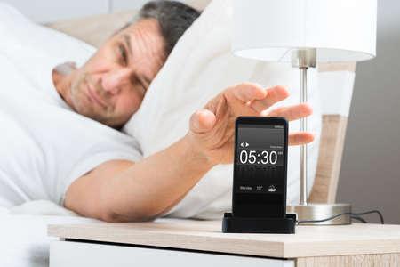 despertador: Hombre maduro en cama con el tel�fono celular en Mesilla de noche Foto de archivo