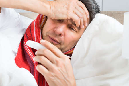 1 person: Portrait Of Mature Sick Man Looking At Thermometer