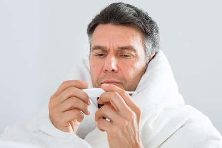 chory: Portret dojrzałym chory zawinąć w koc Patrząc Na Termometr Zdjęcie Seryjne