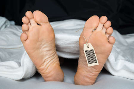 human body parts: Deceased Person Covered In A Sheet With A Toe Tag Stock Photo