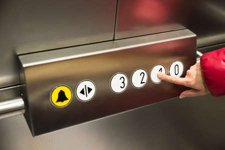Close-up Of A Person In Elevator Pressing The First Floor Button photo