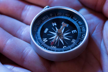 compass rose: Close-up Of Hand Holding Silver Black Compass