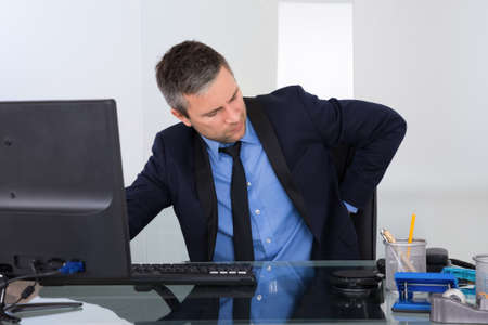 backpain: Portrait Of Businessman Suffering From Backpain In Office Stock Photo