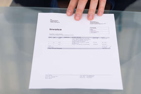 bank records: Close-up Of Persons Hand With Invoice On Desk Stock Photo