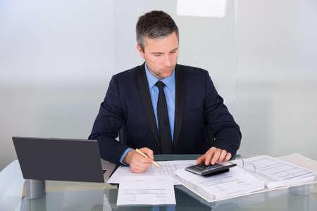 Portrait d'un commerçant Calcul Finances Dans Office Banque d'images - 35943470