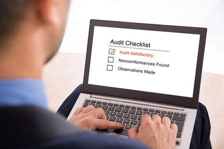 investigación: Primer plano de un empresario Llenar el Formulario de Auditoría Lista de verificación en la computadora portátil Foto de archivo