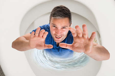 flushed: High Angle View Of A Man With Hand Raised Inside Commode