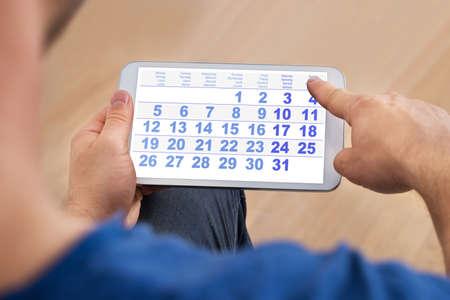 スマート フォンのカレンダーを見て男のクローズ アップ