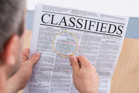 classifieds: Close-up Of A Man Looking Classifieds Through Magnifying Glass