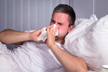 gripe: Hombre infectado con fr�o y gripe que sopla su nariz en papel de seda