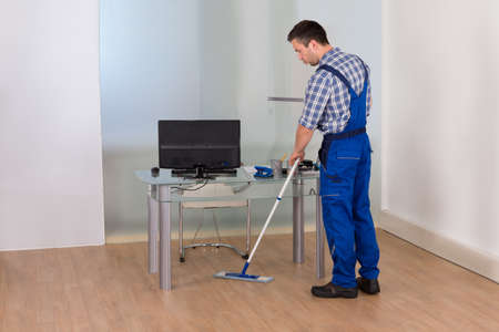 office cleanup: Portrait Of A Male Janitor Cleaning Floor With Mop In Office