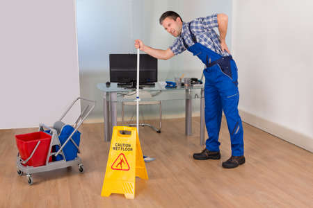 back to work: Male Janitor Suffering From Back Pain While Mopping In Office Stock Photo