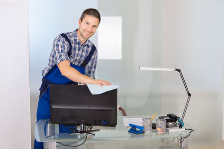 service desk: Portrait Of Happy Male Janitor Cleaning Desktop In Office Stock Photo