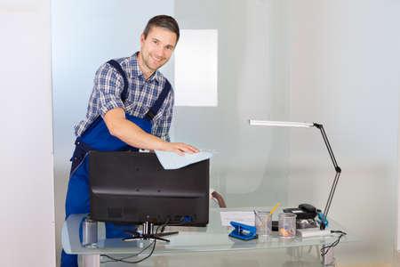 Portrait Of Happy Male Janitor Cleaning Desktop In Office Stockfoto
