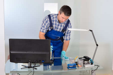 desk tidy: Portrait Of Male Janitor Cleaning Desk In Office Stock Photo