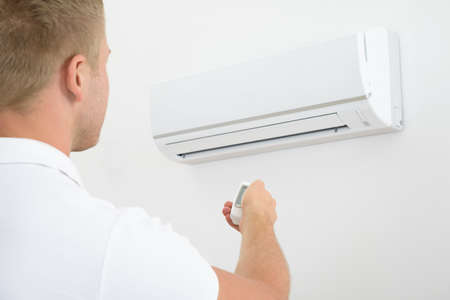 man in air: Man Operating Air Conditioner With Remote Controller