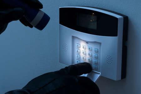 sistema: Ladr�n con la linterna Tratando para desarmar el sistema de alarma de seguridad Foto de archivo