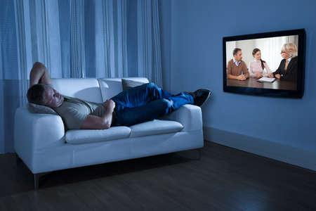 hombre sentado: Hombre que miente en el sof� que ve la pel�cula en casa