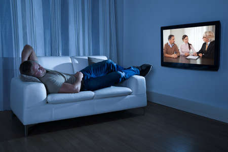 man watching tv: Man Lying On Couch Watching Movie At Home