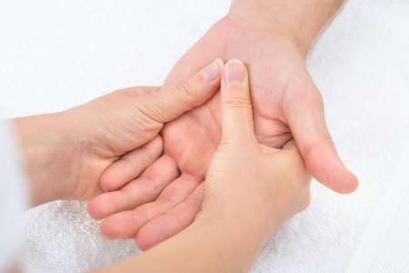 reflexologie: Close-up d'un physiothérapeute Masser Palm Of A Man Banque d'images