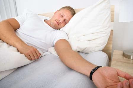 wellness sleepy: Young Man Sleeping On Bed Wearing Smart Wristband