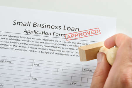 approval rate: Close-up Of Person Hand Holding Approved Rubber Stamp Over Loan Application Form Stock Photo