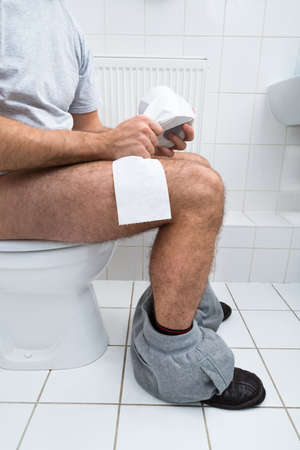 Close-up Of A Man Sitting On Commode Holding Tissue Paper Roll photo