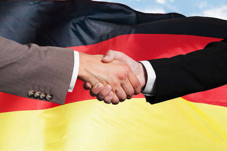 Close-up Of Two Businesspeople Shaking Hands In Front Of German Flag photo