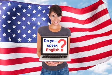 bandera inglesa: Mujer joven que sostiene Pidiendo Laptop habla usted Inglés en frente de la bandera de Usa