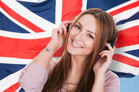 libertad: Mujer que escucha el aprendizaje de idiomas Curso de libros sonoros delante de la bandera brit�nica