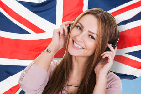 learning: Woman Listening Language Learning Course Audiobook In Front Of British Flag