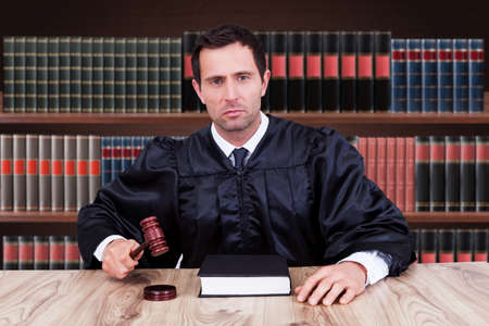 mallet: Portrait Of Serious Male Judge Striking Gavel In Courtroom Stock Photo