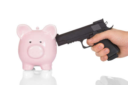 pointing gun: Close-up Hand Pointing Gun At A Piggy Bank Over White Background Stock Photo