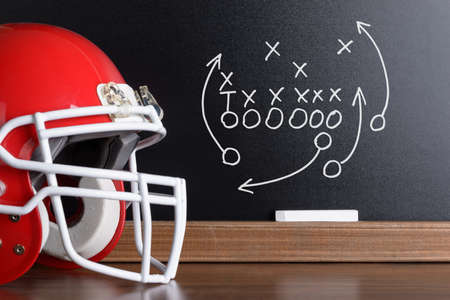 Sport Helmet In Front Of A Chalkboard With Football Play Strategy photo