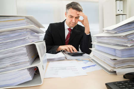 INVOICE: Photo Of Mature Businessman Calculating Invoices In Office