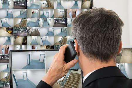 seguridad laboral: Seguridad del Operador del Sistema Mirando a Cctv metraje mientras habla por tel�fono Foto de archivo