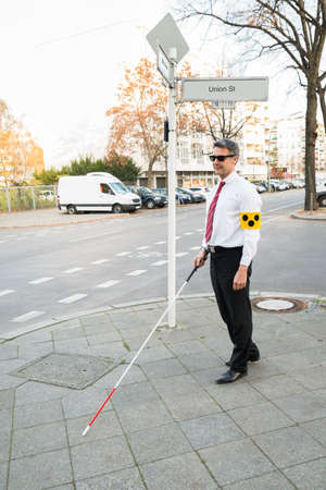 blind man: Blind Man Wearing Armband Crossing Road Holding Stick