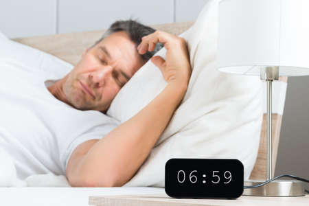 Mature Man Sleeping On White Bed With Clock On Nightstand