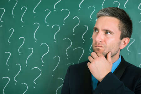contemplated: Thoughtful Businessman In Front Of Chalkboard With Question Mark Sign