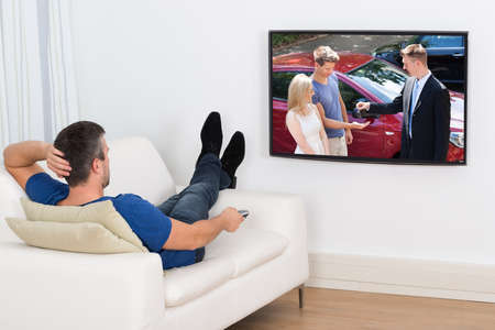 sofa television: Rear View Of A Man Lying On Couch Watching Television Stock Photo