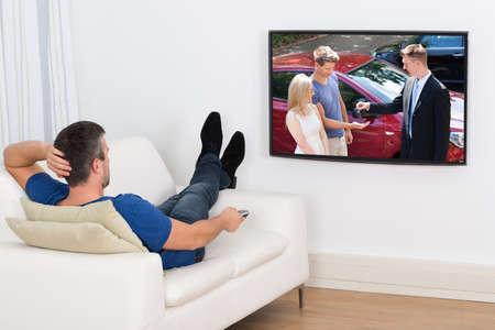 Vista posterior de un hombre tumbado en el sofá Televisión de observación Foto de archivo