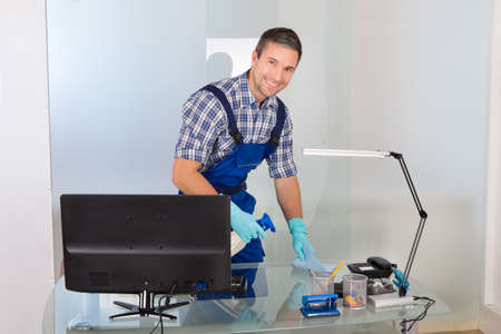 janitor: Portrait Of A Happy Male Janitor Cleaning Desk In Office