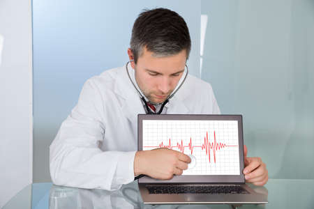 examining: Male Doctor Examining Laptop Screen Displaying Electrocardiogram