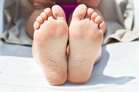 Closeup of young woman's bare feet tanning at resort