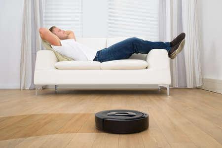 robot: Hombre que se relaja en el sofá con aspirador robótico En Suelo de madera