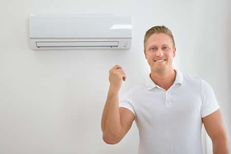heat home: Portrait Of A Man Operating Air Conditioner With Remote Controller Stock Photo
