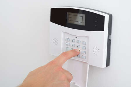 security monitoring: Security Alarm Keypad With Person Arming The System Stock Photo