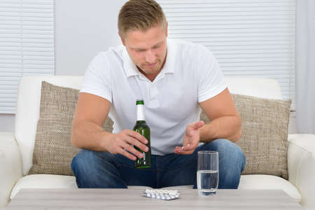 hand holding pills: Man Sitting On Couch Looking At Pills And Holding Bottle In Hand