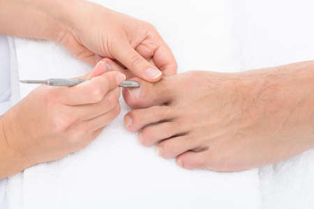 Close-up Of Manicurist Removing Cuticle From The Nails Of Feet