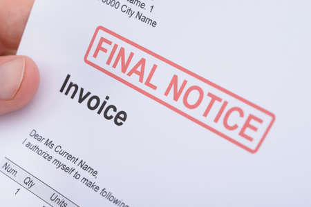 Close-up Of A Man Holding Invoice With Final Notice Stamp On It